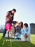 Lifestyle and Leisure photo of a family having fun together in the park with the family dog. Mother, father, son, and daughter. Blue sky and green grass.